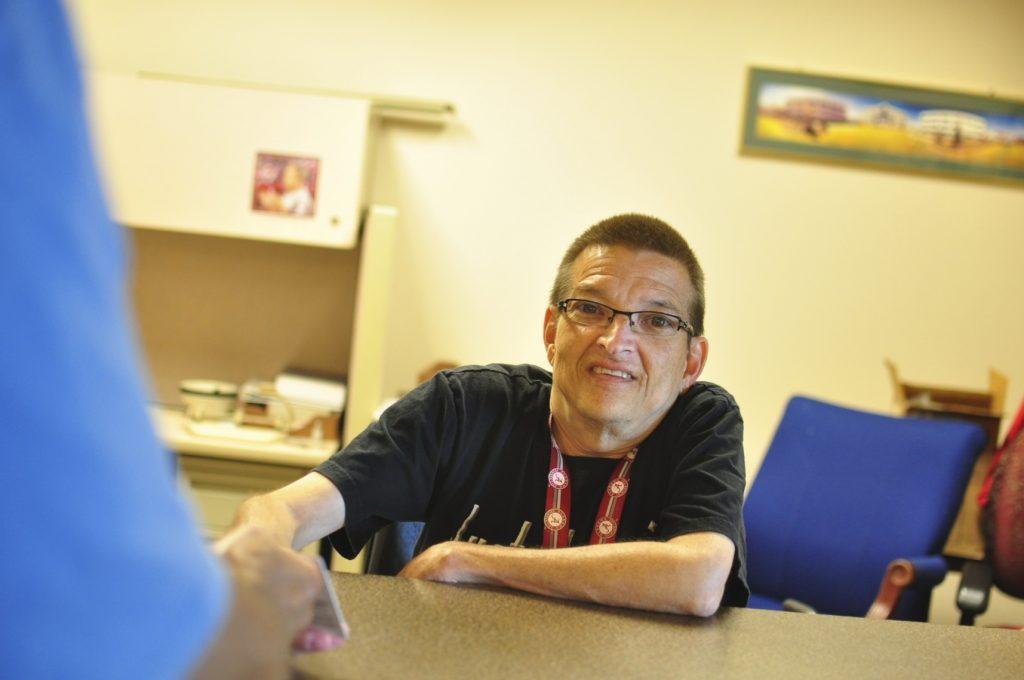 Man Checking Badges at Desk